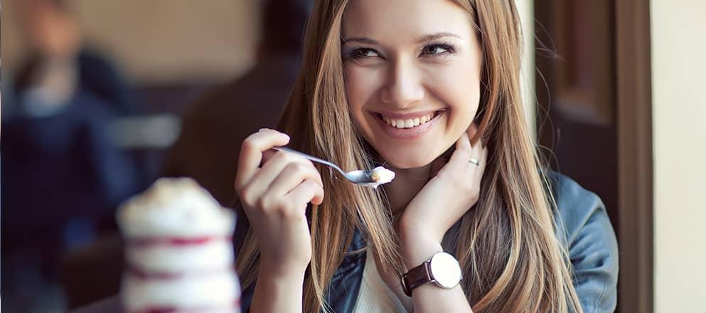 Vrouw eet lachend een stukje ijs