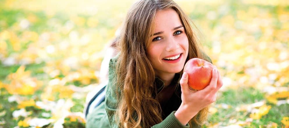 Een vrouw met diabetes ligt lachend in het gras terwijl ze een perzik eet