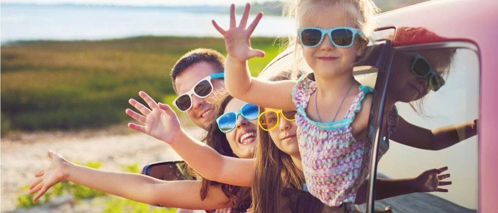 Een gezin op reis hangt vrolijk uit het autoraam