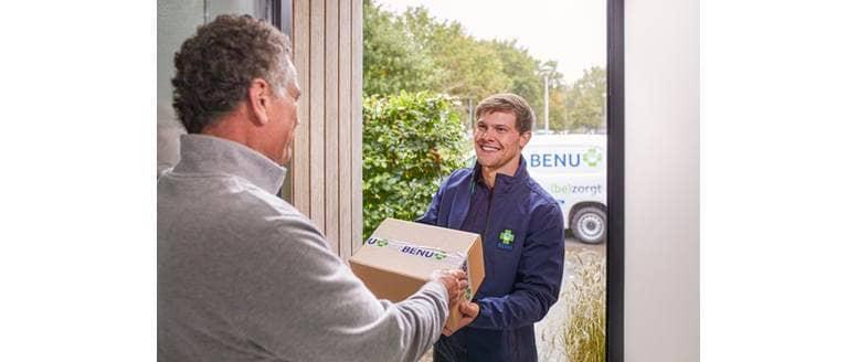 Bezorger van BENU Direct brengt een pakje aan de deur van de klant
