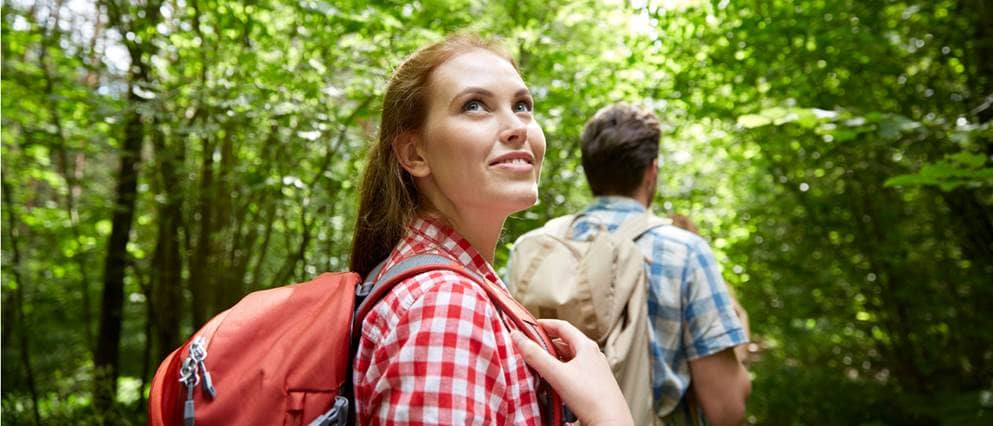 Jonge vrouw maakt een boswandeling en kijkt ontspannen.