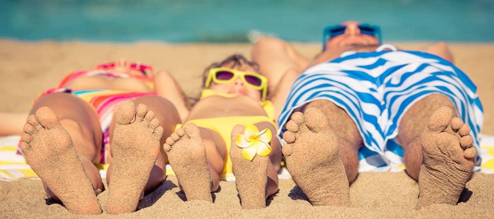 Gezin ligt op het strand te zonnen.