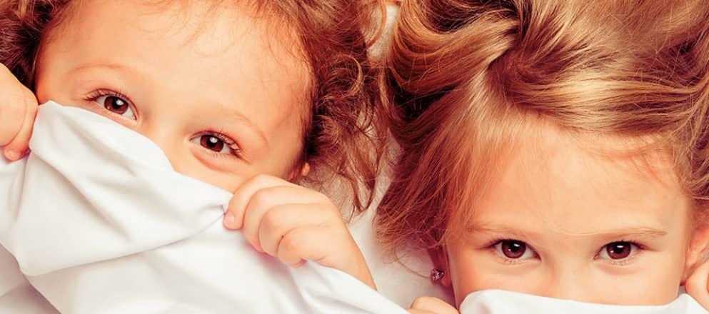 kinderen met hun hoofd net boven de lakens