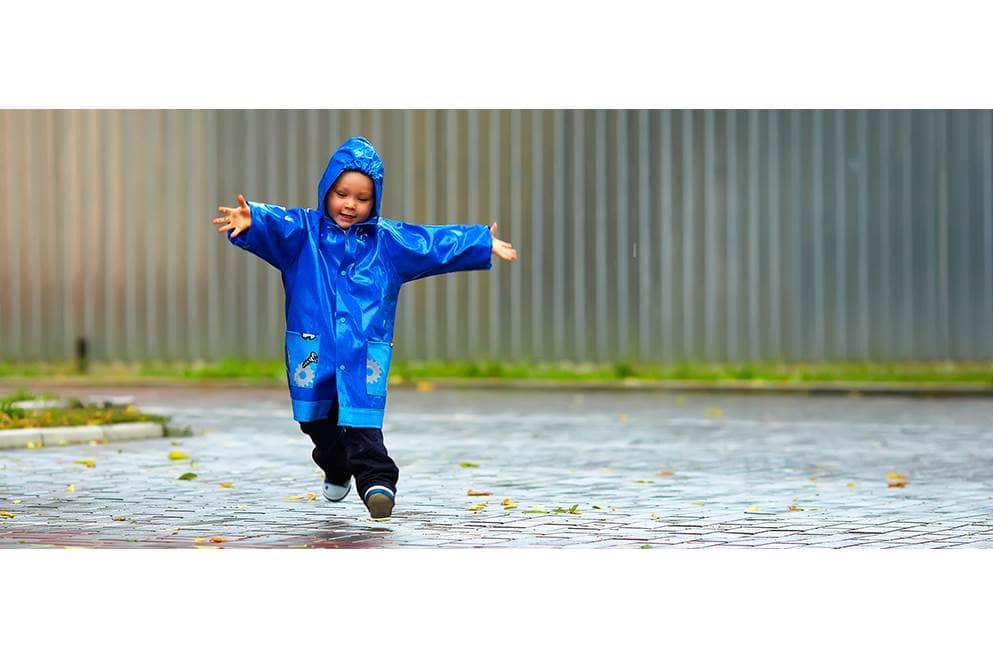 kind speelt in de regen
