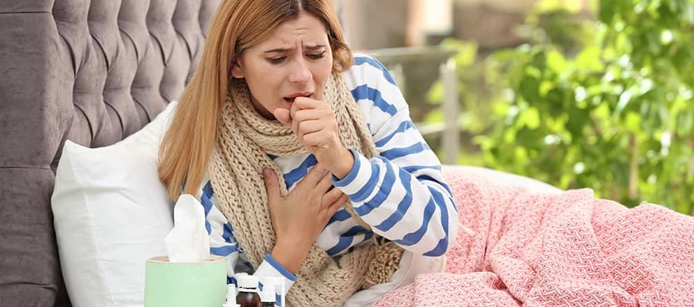 Vrouw ligt in bed onder roze deken en moet erg zwaar hoesten