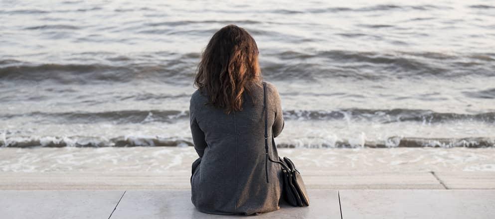 Vrouw kijkt vanaf de boulevard uit  op zee