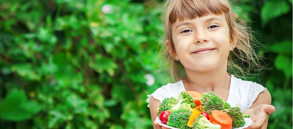 Kindje met groente op haar bord
