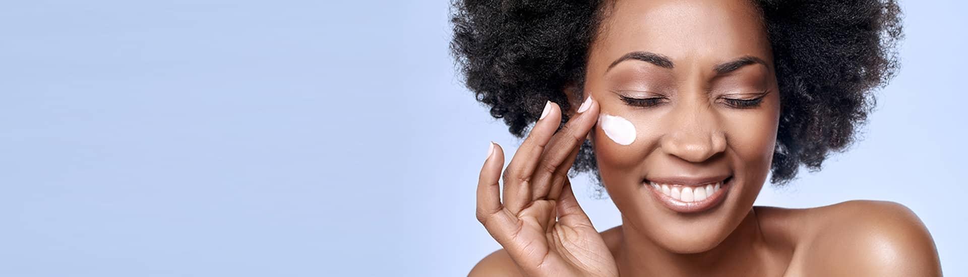 Vrouw veegt crème op haar huid