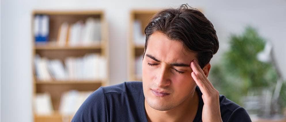 Man heeft zichtbaar last van hoofdpijn.