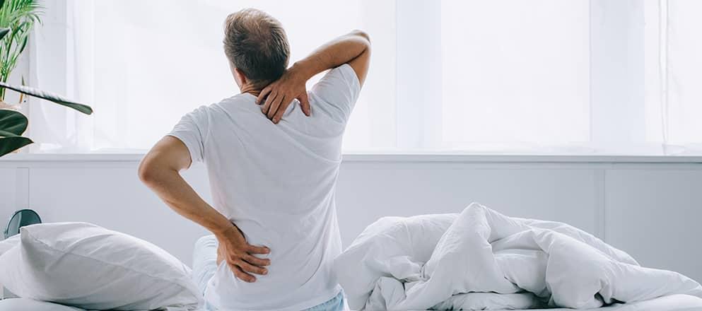 Man zit op bed met last van zijn rug en nek