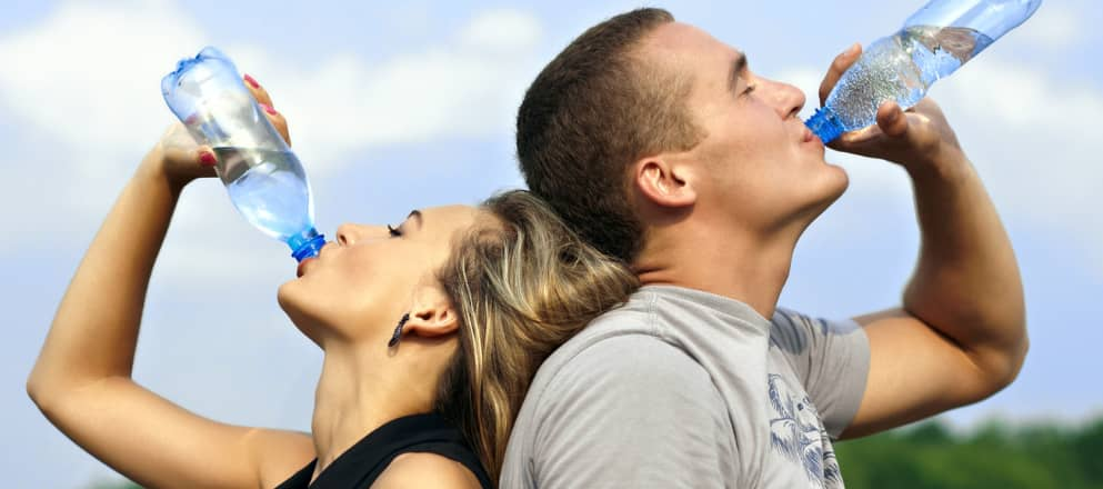 Twee jonge mensen drinken hun flesje water leeg.