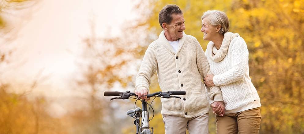 Ouder koppel lopen arm in arm door het bos met fiets in de hand