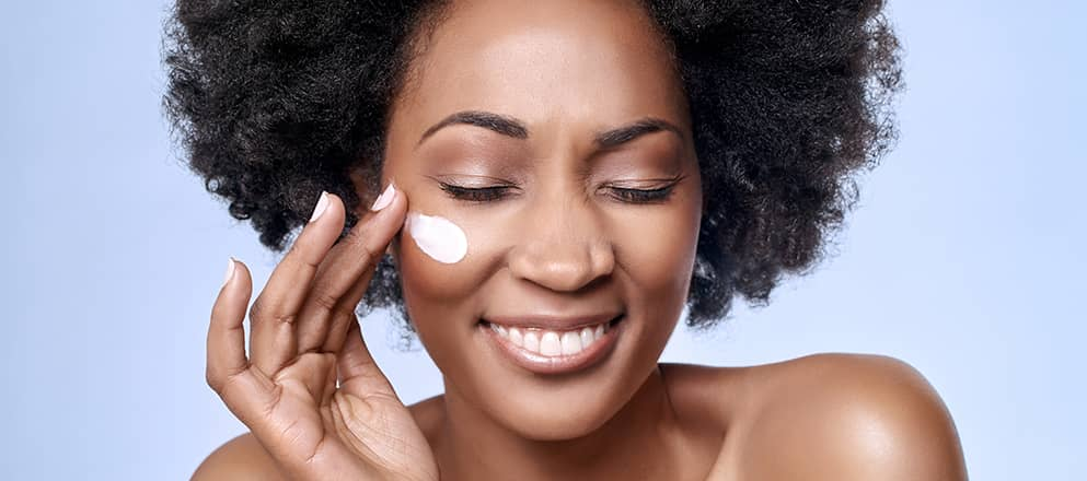 vrouw smeert crème op haar gezicht