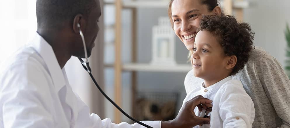 De arts luistert naar de longen van een kind.