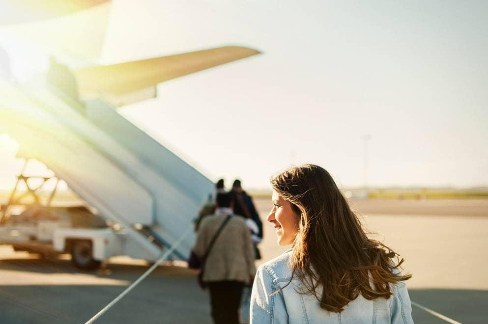 vrouw loopt naar vliegtuig