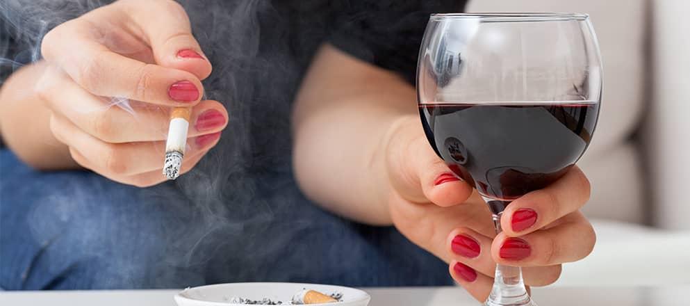 Een vrouw met een sigaret en een glas wijn in haar handen