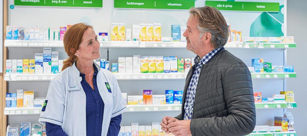 man krijgt advies bij balie in apotheek