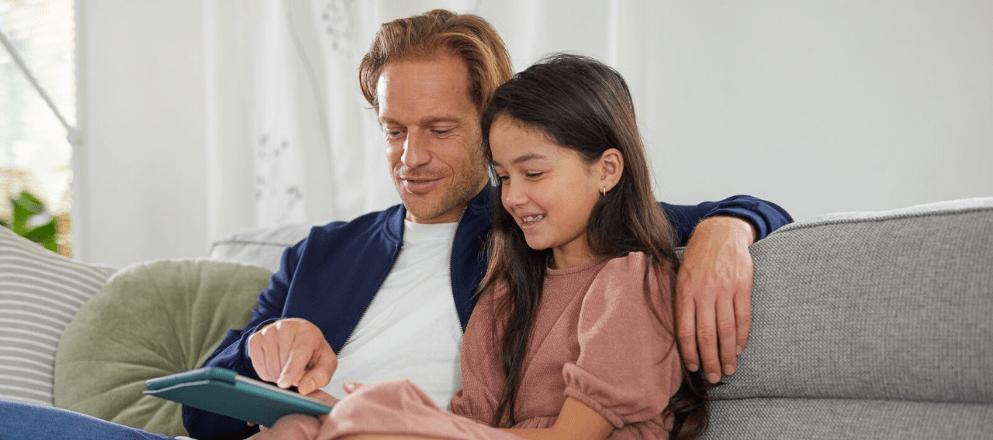 Vrouw zit op de bank met dochter en haar laptop