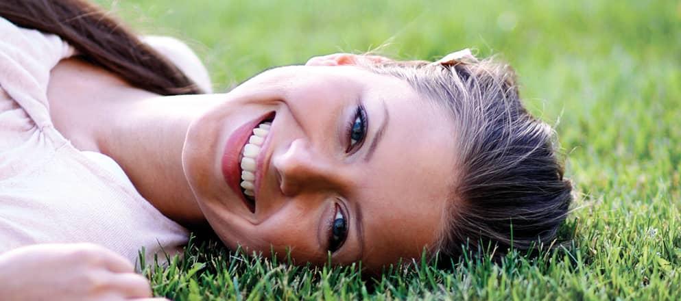 Een jonge vrouw met hooikoorts ligt lachend in het gras