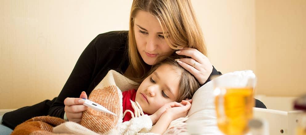 Jongetje met bronchitis ligt ziek op bed met moeder die temperatuur opneemt