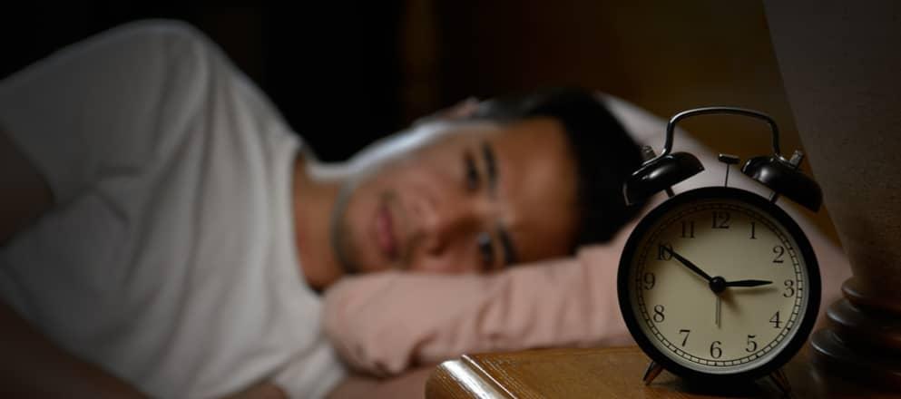Man ligt naar de wekker te kijken midden in de nacht