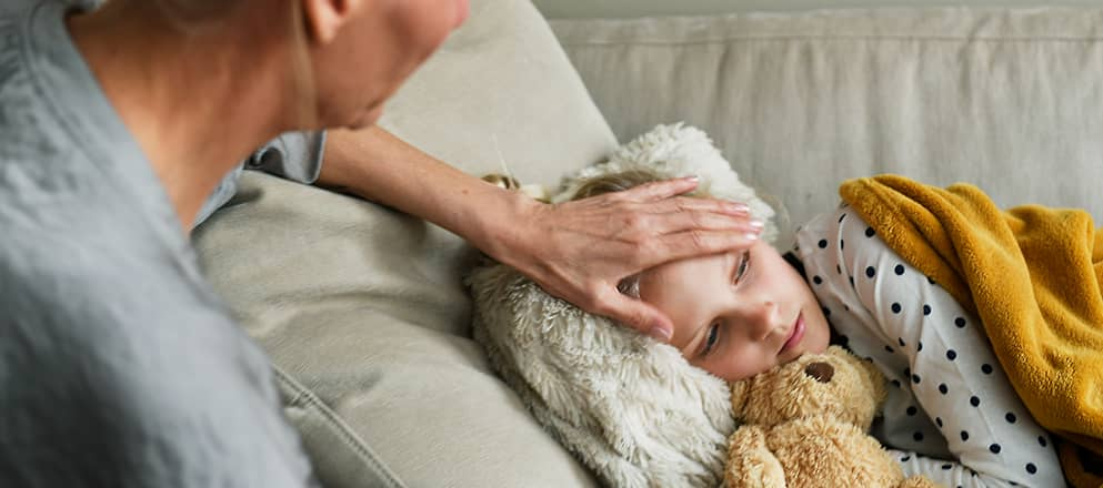 Kindje ligt ziek op de bank en moeder neemt temperatuur op