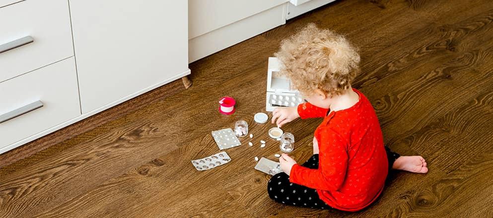 Kindje speelt met medicijnen op de vloer