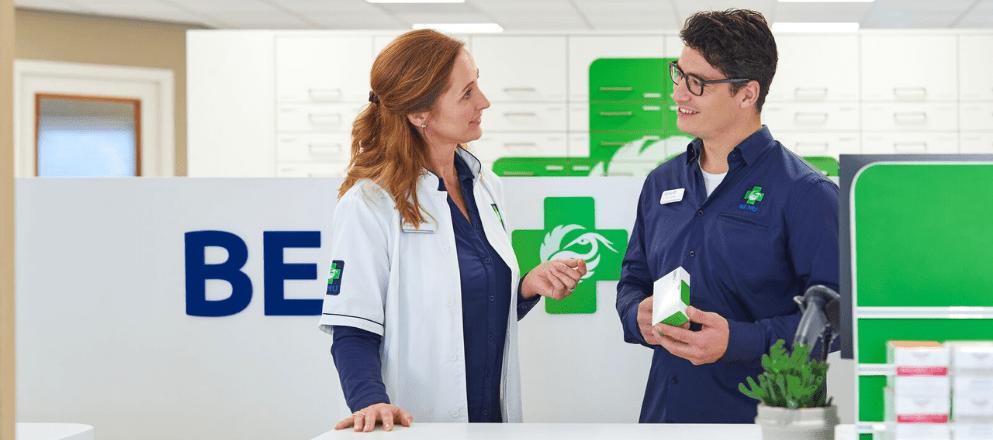 Een apotheker en medewerker die een klant helpen