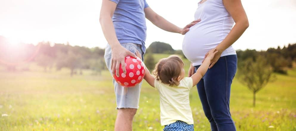 Familie buiten met zwangere mama