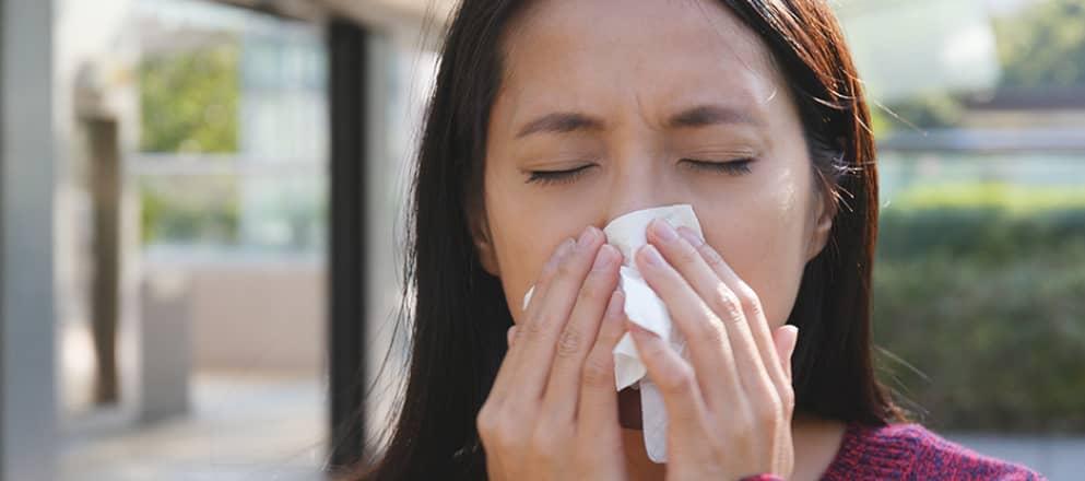 vrouw snuit haar neus