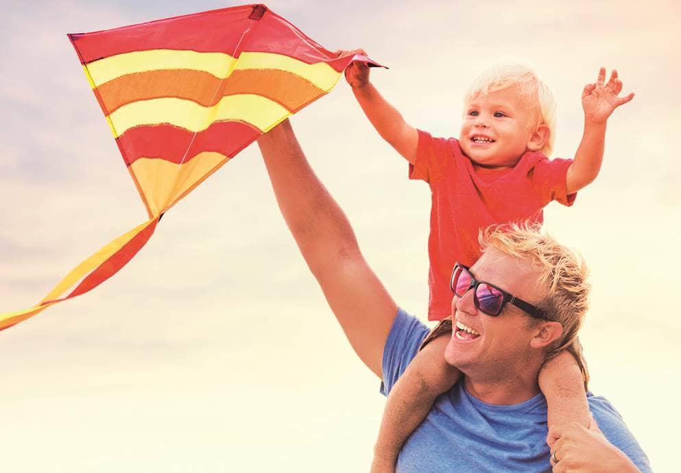 man aan het vliegeren met zoon