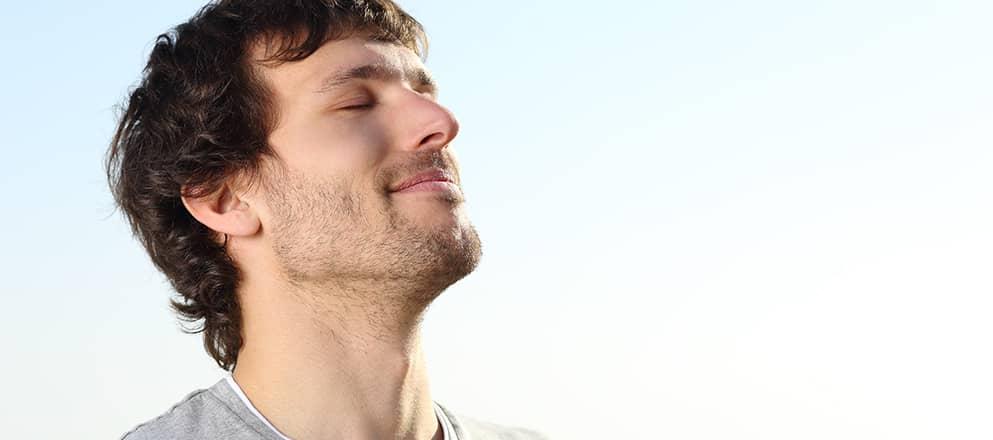 Een man met astma haalt opgelucht diep adem