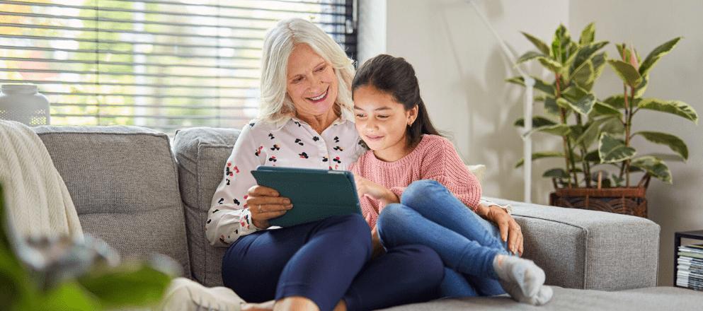 Vrouw en zorgprofessional staan in het park en kijken elkaar lachend aan