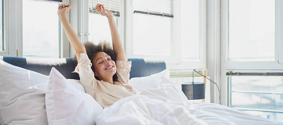 Vrouw rekt zich uit in bed