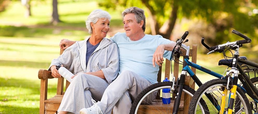 ouder echtpaar pauzeert op een bankje tijdens het mountainbiken