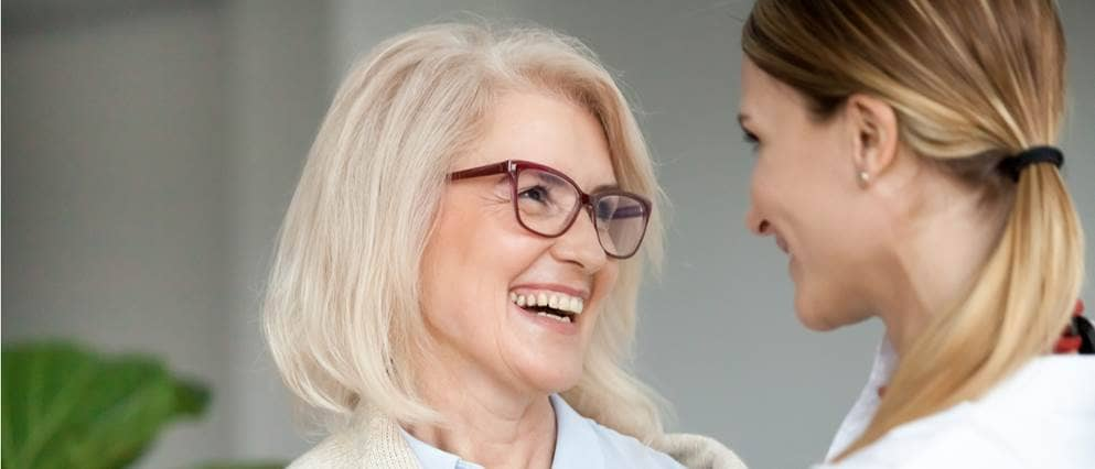 Dame van middelbare leeftijd lachend in gesprek met haar dochter