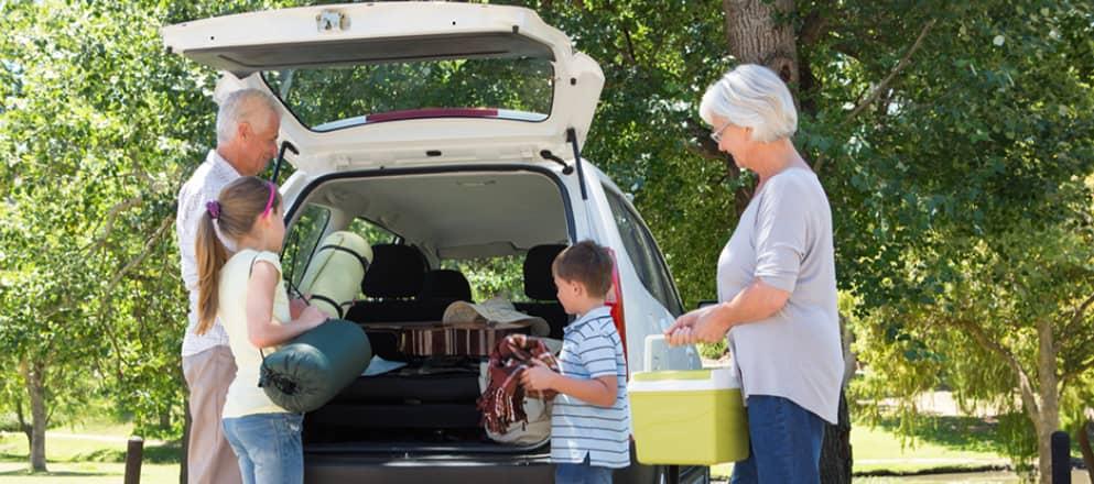 Familie pakt auto in voor een kampeervakantie.