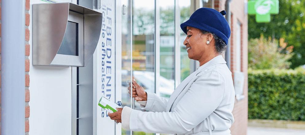 Vrouw met dochter die medicijnen afhaalt bij de afhaalautomaat