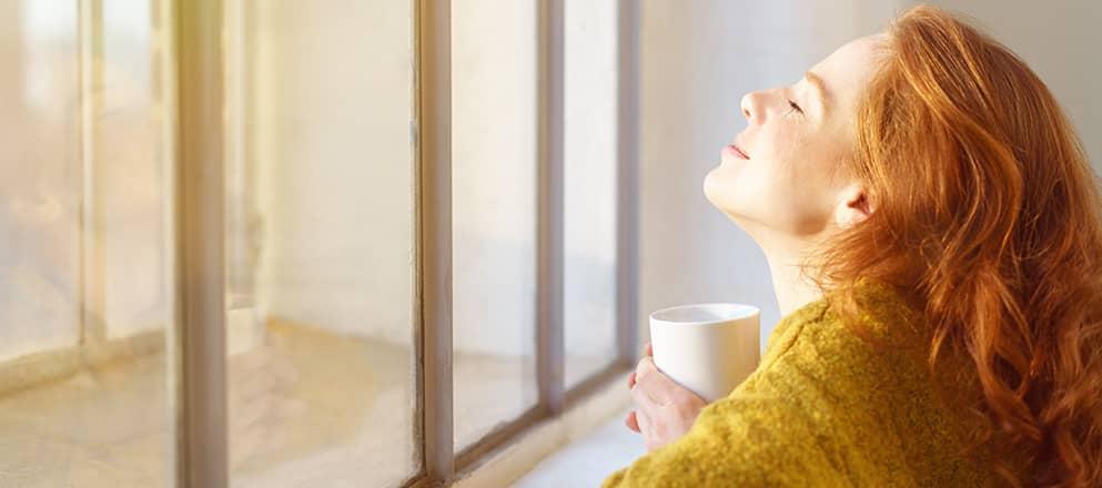Vrouw die geniet van de zon voor het raam