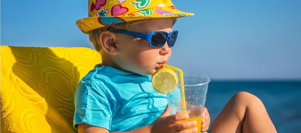 Jongen van 3 jaar drinkt limonade in de zon op het strand.