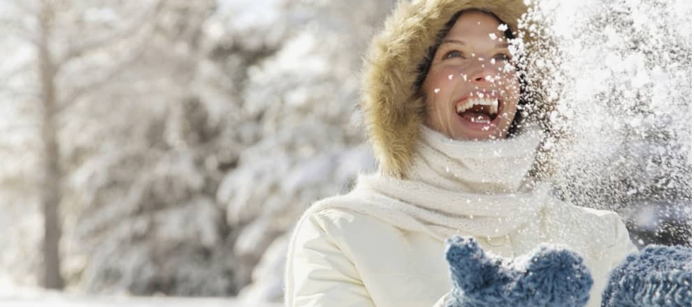 Vrouw gooit sneeuw in de lucht