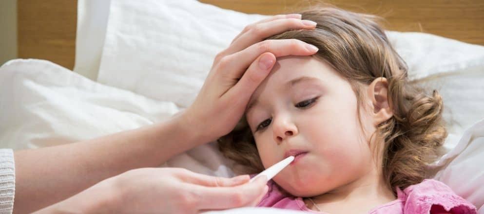 moeder neemt temperatuur op van jongen met griep