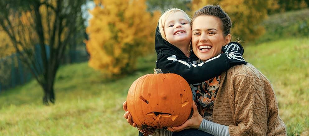 Moeder en zoontje met een versierde pompoen tijdens Halloween