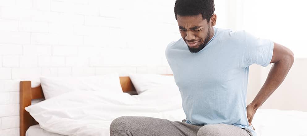 Man met rugpijn staat op uit bed